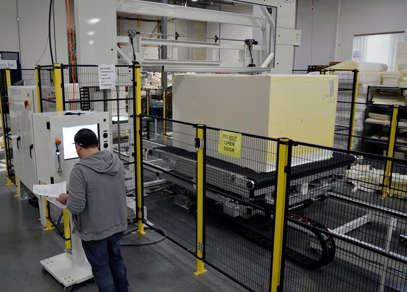 A bun of foam is sliced and sculpted in Alpha Tekniko's CNC foam cutting department.