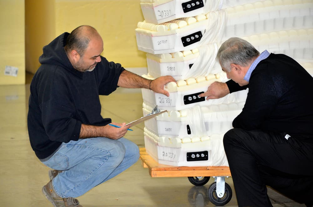 Ted Lazakis confirms placement and function of microclimate mattress components with an Alpha Tekniko employee.